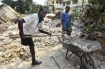 A Port-au-Prince man is in the process of shoveling, transporting and dumping the debris