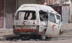 A destroyed Syrian Arab Red Crescent ambulance sits amid rubble in Homs