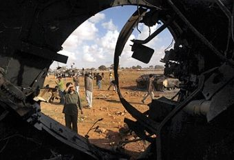 A man looks at a destroyed tank belonging to Gaddafi forces after an air strike by coalition forces