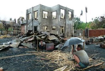 Two men sit under the the remnants of their homes in Sittwe, the provincial capital of Myanmar's western Rakhine State.