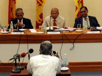 Former Sri Lankan diplomat Bernard Gunathilaka (back to camera) gives testimony to LLRC