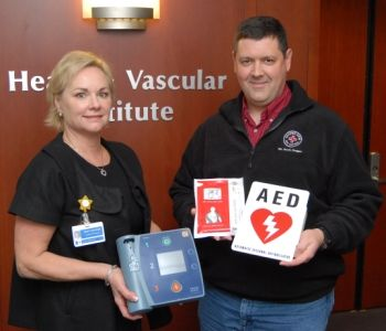 Providence Heart and Vascular Institute administrator Kristy Wayson and Cooper Spur Volunteer Ski Patrol member Jason Wilkins display the donated AED.