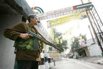 Fatah member stands guard at the entrance of the Palestinian refugee camp of Ain al-Hilweh