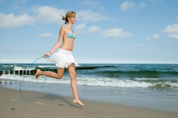 Woman jumping rope on beach
