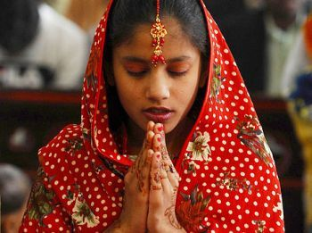 A Pakistani Christian girl prays as she attends a Christmas service.