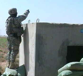 A U.S. Army soldier in Iraq motions toward an approaching individual while on patrol.