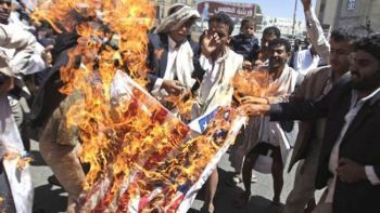Yemenis burning the US flag during a demonstration