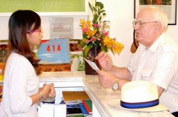 The file photo shows Mr. Len Adis (R) asking an employee of Monsanto to send his letter to the director of Monsanto's representative office in Vietnam in 2009. (Photo: SGGP)