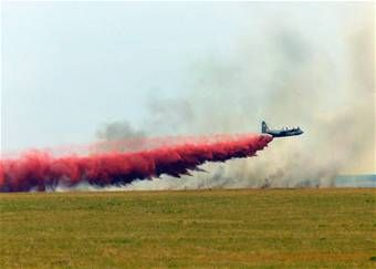 A C-130 Hercules aircraft drops fire retardant chemicals on a wildfire.  Photo: California Air National Guard