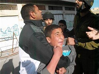 Israeli forces detain a child in Hebron, March 20. (MaanImages/B'Tselem, HO)