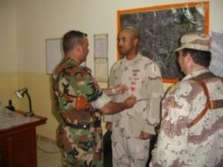 Iraqi Army Staff Major Mohammed presenting the Bronze Star Medal to Captain James Văn Thạch and Iraqi Army Major Ihsan is standing to the right.