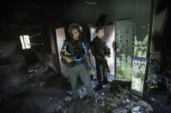 Israeli policemen inspect a burnt mosque after it was torched in the Bedouin village of Tuba Zangaria (AFP/File, Menahem Kahana)