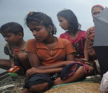 Rohingya refugees cross the Naf River in a downpour
