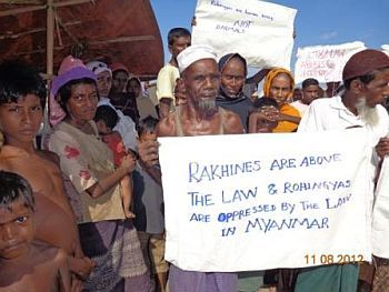 Rohingya people hold signs begging for world help
