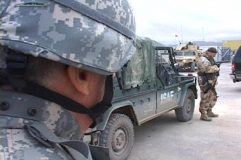 An American soldier looks toward in International Security Assistance Forces vehicle and a British soldier.