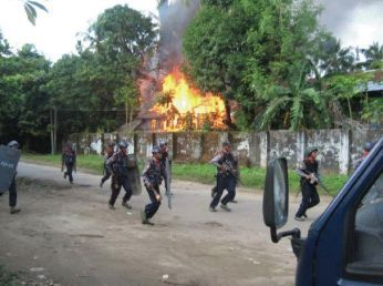 File photo of government forces in a burning Sittwe village