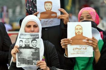 Demonstrators in the West Bank city of Nablus hold posters in solidarity with hunger striking prisoners