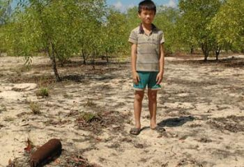 Duong Ba Tien with the unexploded bomb he found while tending his family's water buffalo in Quang Tri province, central Vietnam. Photograph: Simon Cordall